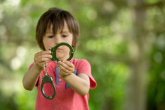 O rapaz pequeno bonito com a mão cuffs em suas mãos foto de stock