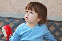 O rapaz pequeno bonito com um chocalho vermelho fotos de stock