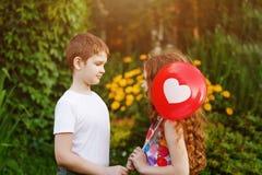 O rapaz pequeno bonito com vermelho do presente balloons sua menina do amigo Imagem de Stock
