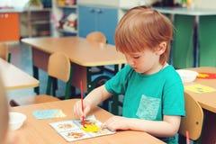 O rapaz pequeno bonito contratou na arte e no ofício na sala de aula Conceito da aprendizagem e da educação fotos de stock