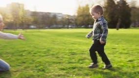 O rapaz pequeno bonito corre para serir de mãe no abraço, salta parque no por do sol video estoque