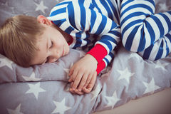 O rapaz pequeno bonito dorme nos pajames na cama Fokus acima Foto de Stock Royalty Free