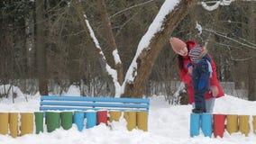 O rapaz pequeno bonito e a mãe nova jogam no inverno com neve no parque Revestimento azul e vermelho do ` s da criança na mamã filme
