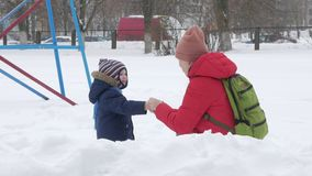 O rapaz pequeno bonito e a mãe nova jogam no inverno com neve no parque Revestimento azul e vermelho do ` s da criança na mamã vídeos de arquivo