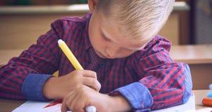 O rapaz pequeno bonito em uma camisa quadriculado vermelha e tira com uma caneta com ponta de feltro em um caderno da escola fotografia de stock royalty free