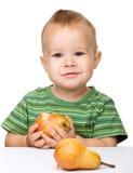 O rapaz pequeno bonito está comendo a pera Fotografia de Stock Royalty Free