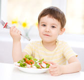O rapaz pequeno bonito está comendo a salada vegetal Imagem de Stock Royalty Free