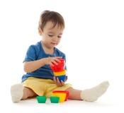 O rapaz pequeno bonito está jogando com copos coloridos Imagens de Stock Royalty Free