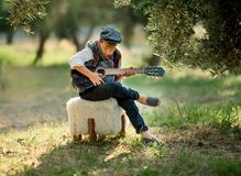 O rapaz pequeno bonito está jogando a guitarra no parque fotos de stock royalty free