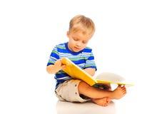 O rapaz pequeno bonito está lendo um livro foto de stock
