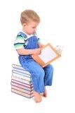 O rapaz pequeno bonito está lendo um livro fotografia de stock