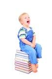 O rapaz pequeno bonito está lendo um livro Imagens de Stock
