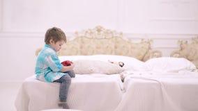 O rapaz pequeno bonito está sentando-se no quarto na cama e está guardando-se um despertador Acorde o conceito O menino está joga vídeos de arquivo