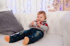 O rapaz pequeno bonito está sentando-se no sofá em casa imagens de stock