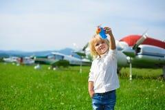 O rapaz pequeno bonito joga com um avião do brinquedo no aeroporto Imagens de Stock