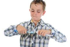 O rapaz pequeno bonito limpa seus dentes Imagem de Stock