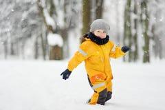 O rapaz pequeno bonito na roupa amarela do inverno anda durante uma queda de neve imagens de stock