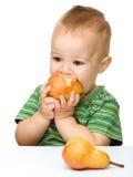 O rapaz pequeno bonito é pera cortante Foto de Stock