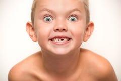 O rapaz pequeno cai para fora um dente de bebê Esperas da criança para a fada de dente foto de stock