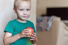 O rapaz pequeno caucasiano bonito com olhos azuis e cabelo louro em t-curto verde come a maçã vermelha, guardando o nas mãos fotografia de stock