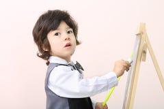 O rapaz pequeno com ponteiro amarelo tira com giz no quadro Imagens de Stock Royalty Free