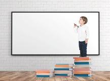O rapaz pequeno com um marcador em livros empilha o whiteboard imagem de stock royalty free