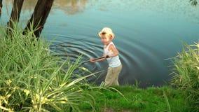 O rapaz pequeno com uma haste vai em casa após a pesca O rapaz pequeno em uma camiseta branca vídeos de arquivo