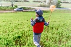 O rapaz pequeno com uma rede da borboleta corre à disposição através do campo verde fotografia de stock royalty free