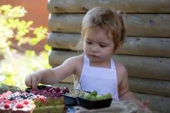 O rapaz pequeno come a framboesa vermelha Foto de Stock