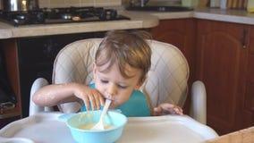 O rapaz pequeno come o papa de aveia para o café da manhã filme