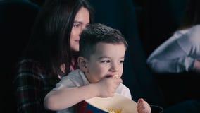 O rapaz pequeno come a pipoca no cinema vídeos de arquivo