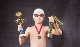 O rapaz pequeno comemora seu troféu dourado na natação foto de stock