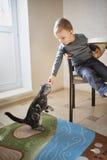 O rapaz pequeno compartilha do alimento com o gato imagens de stock