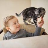 O rapaz pequeno compartilha do alimento com o gato imagens de stock royalty free