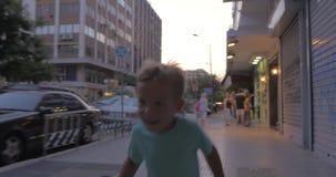 O rapaz pequeno corre ao longo de uma rua movimentada de Tessalónica, Grécia filme