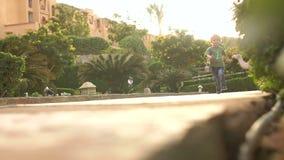 O rapaz pequeno corre no parque no verão, slowmo vídeos de arquivo