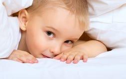 O rapaz pequeno da criança está encontrando-se na cama sob a cobertura Fotos de Stock Royalty Free