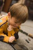 O rapaz pequeno de sorriso joga o jogo da lógica no PPC Fotos de Stock Royalty Free