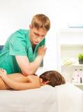 O rapaz pequeno descansa com os termas na tabela da massagem fotos de stock royalty free