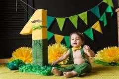 O rapaz pequeno do aniversário senta-se perto da figura do número um Imagens de Stock Royalty Free