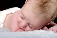 O rapaz pequeno dorme em um cobertor branco Fotos de Stock
