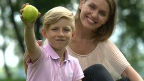 O rapaz pequeno e a mãe de inquietação que guardam a maçã, família representam a nutrição saudável filme