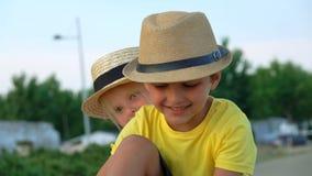 O rapaz pequeno e a menina estão sorrindo na câmera vídeos de arquivo