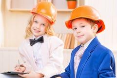 O rapaz pequeno e a menina estão vestindo capacetes protetores Imagem de Stock Royalty Free