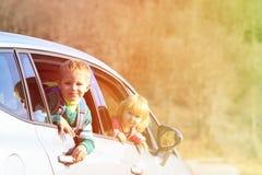 O rapaz pequeno e a menina felizes viajam pelo carro na natureza Imagem de Stock