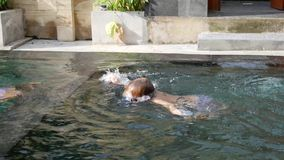 O rapaz pequeno e a menina nadam debaixo d'água na piscina vídeos de arquivo