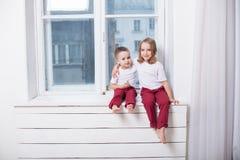 O rapaz pequeno e a menina sentam-se na soleira que olha para fora a janela foto de stock
