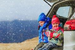 O rapaz pequeno e a menina viajam pelo carro em montanhas do inverno Fotos de Stock