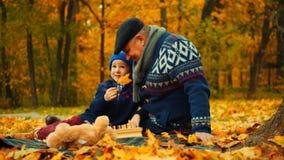 O rapaz pequeno e seu avô estão sentando-se no parque do outono e estão jogando-se com folhas fotografia de stock
