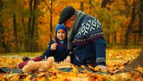 O rapaz pequeno e seu avô estão sentando-se no parque do outono e estão jogando-se com folhas Foto de Stock